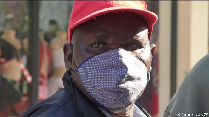 Carlos Mavanga wears a mask as he waits in line to receive social benefits