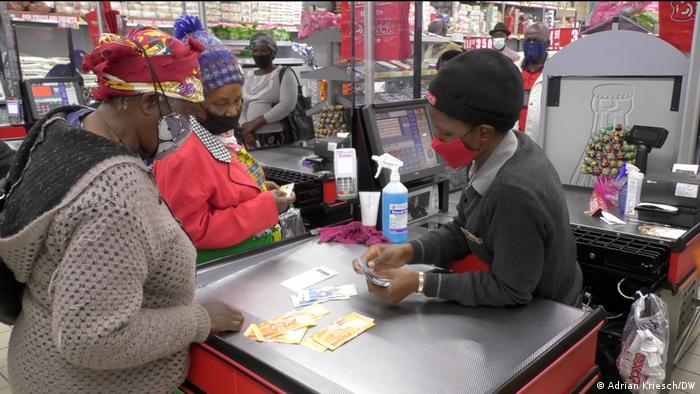 Two women in South Africa receive their social benefit handout at a supermarket checkout