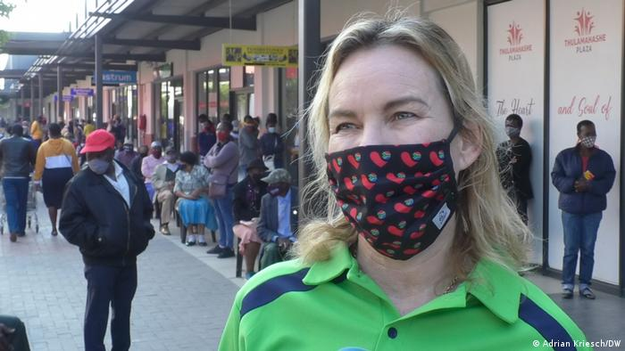 Jane Simmonds from the South African Medical Research Council stands in front of a vaccine queue wearing a mask