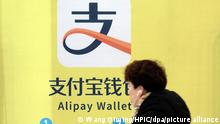 ARCHIV 2018 *** --FILE--A pedestrian walks past an advertisement for Alipay Wallet, the mobile payment service of Chinese e-commerce giant Alibaba's Ant Financial, at a metro station in Nanjing city, east China's Zhejiang province, 9 February 2018. Ant Financial's consumer lending has reached at least 600 billion yuan ($95 billion) despite the affiliate of Alibaba Group Holding Ltd. facing a tougher environment for securitizing its loans, people familiar with the matter said. From the start of 2017 until this month, Ant's consumer lending has doubled via its Huabei and Jiebei units even as the government reduces quotas for new asset-backed securities that can underpin such loans, one of the people said, asking not to be named as the matter is private. The loans can incur annual interest rates as high as 15 percent, although they are normally less than that, another person said.