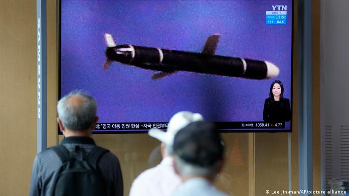 South Koreans watch a rocket on TV