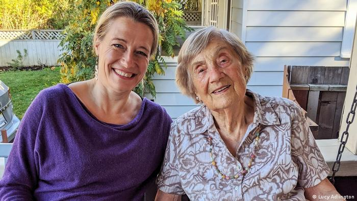 A younger and older woman sit together smiling on a porch
