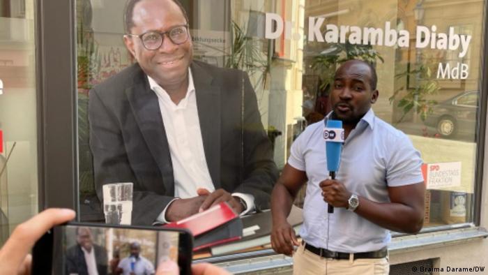 DW-Journalist Harrison Mwilima steht vor dem Büro von Karamba Diaby mit einem DW Mikrophon in der Hand.