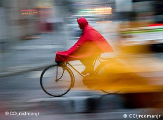A cyclist in a red raincoat in the rain in Shanghai