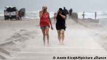 People shield their faces from wind and sand ahead of Tropical Storm Nicholas, Monday, Sept. 13, 2021, on the North Packery Channel Jetty in Corpus Christi, Texas. Lifeguards paroled the beach to warn people of the upcoming conditions. (Annie Rice/Corpus Christi Caller-Times via AP)
