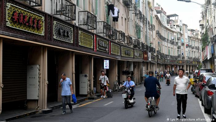 People walk by arcade buildings in the old district on August 28, 2020 in Xiamen, Fujian Province of China