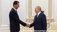 Russian President Vladimir Putin, right, greets Syrian President Bashar Assad during their meeting in the Kremlin in Moscow, Russia, Monday, Sept. 13, 2021. (Mikhail Klimentyev, Sputnik, Kremlin Pool Photo via AP)