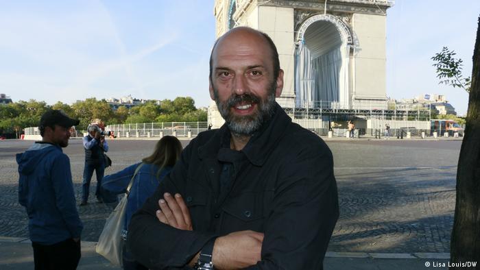 Vladimir Yavachev, man, arms crosed, smiles into camera, behind him the Arc de Triomphe