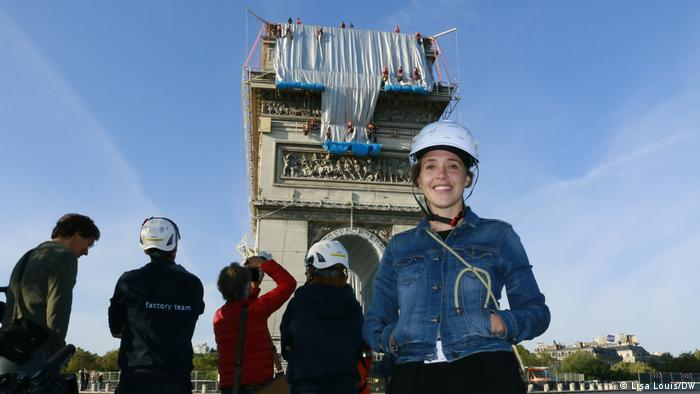 A smiling woman in a white hard hat in from of a large monument