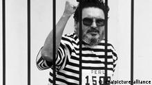 Abimael Guzman, der Anführer der maoistischen Terrororganisation Leuchtender Pfad, am 24. September 1992. Zwei Wochen nach seiner Festnahme ist der Anführer der maoistischen Terrororganisation Leuchtender Pfad (Sendero Luminoso), Abimael Guzman, am 24. September 1992 der Presse vorgeführt worden. Aus einem Käfig im Hof des Hauptquartiers der Antiterror-Polizei DINCOTE in Lima rief der Guerillachef im schwarz-weiß gestreiften Sträflingsanzug, dem Leuchtenden Pfad stehe im Volkskrieg der Endsieg bevor. Nach seiner Rede stimmten die Journalisten die peruanische Nationalhymne an, Guzman antwortete darauf mit geballter Faust. Aufgrund der Anti-Terror-Dekrete der Regierung Fujimori wurde Guzman am 26.9.1992 einem Militärtribunal überstellt. |