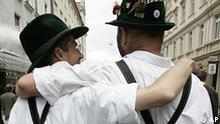 FILE - Teilnehmer der Christopher Street Day Parade in Muenchen, spazieren in bayerischen Trachten am Samstag, 12. August 2006, in der Muenchner Innenstadt. Homosexuelle Lebenspartner duerfen bei der Erbschaftssteuer nicht gegenueber Ehepaaren benachteiligt werden. Das sei mit dem Grundgesetz nicht vereinbar, entschied das Bundesverfassungsgericht in einem am Dienstag, 17. August 2010, veroeffentlichten Grundsatzbeschluss. (AP Photo/Chritsof Stache) --- Participants of the Christopher Street Day dressed in typically Bavarian clothes walk embraced during the parade through the city of Munich, southern Germany, on Saturday, Aug. 12, 2006. (AP Photo/Christof Stache) ** zu APD6831 **
