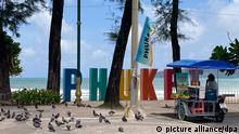Eine Streetfood-Verkäuferin wartet auf Kunden - doch es sind nur Tauben da. Am 1. Juli hat die größte Insel Thailands ihr mit Spannung erwartetes Corona-Modellprojekt «Sandbox» zur Wiederbelebung des Tourismus gestartet. Seither ist Phuket weltweit eines der wenigen Fernziele, wo Menschen aus fast 70 Ländern quarantänefrei Ferien machen können - sofern sie vollständig geimpft sind. (zu dpa-Korr Keine Party auf Phuket: Eine Trauminsel als Pilotprojekt) +++ dpa-Bildfunk +++