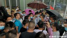 People gather outside the Evergrande headquarters in Shenzhen, southeastern China on September 14, 2021, as the Chinese property giant said it is facing unprecedented difficulties but denied rumours that it is about to go under. (Photo by Noel Celis / AFP)