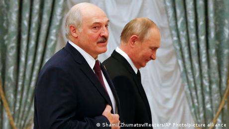 Alexander Lukashenko looking wistful in front of a grinning President Vladimir Putin