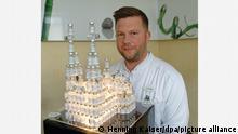 Der Kölner Arzt Bastian Kirsch sitzt neben einem Modell des Kölner Doms, das er aus 220 leeren Impfflaschen gebaut hat.