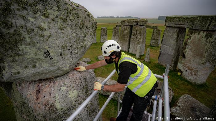 Conservator James Preston uses a pointing spoon atop scaffold erected inside the stone circle at Stonehenge