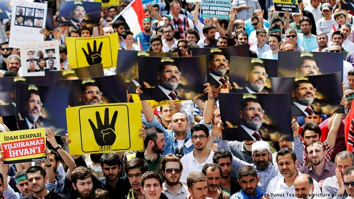 People hold pictures of Mohamed Morsi and the four fingered salute associated with the killing of Muslim Brotherhood supporters in August 2013 during a protest in Istanbul