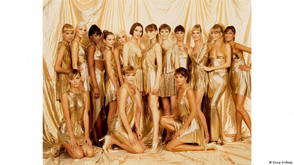 Models tragen goldene Outfits und posieren vor einem goldenen Vorhang.