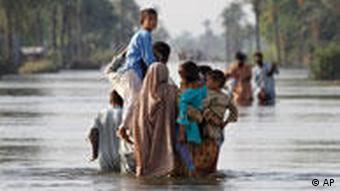 A Pakistani family makes their way through flooded streets in Muzaffargarh near Multan, Pakistan