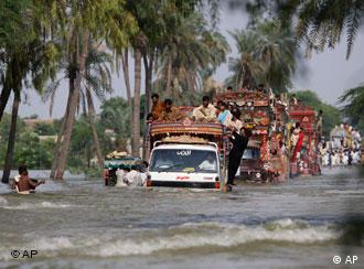 Vehicles loaded with people cross flooded streets in Multan, Pakistan