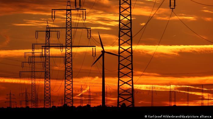 Windrad und Stromtrassen in der Abenddämmerung