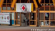 Treuen, 14.09.2021 - Eine Rot-Kreuz-Fahne hängt über dem Eingang zum Impfzentrum in Eich. Im sächsischen Vogtlandkreis hat es einen Brandanschlag auf ein Impfzentrum gegeben. Drei Unbekannte sollen am Dienstagabend Bierflaschen mit einer brennbaren Flüssigkeit auf das Gebäude in Treuen geworfen haben, wie die Polizei am Mittwochmorgen mitteilte.