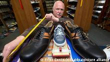 Schuhmacher Georg Wessels hält am 15.04.2013 in Vreden (Nordrhein-Westfalen) ein Maßband an Herrenschuhe mit der Übergröße 66. Dazwischen zum Vergleich ein handelsüblicher Schuh in Normalgröße. Der Schuhmacher aus dem Münsterland fertigt für große Menschen in der ganzen Welt Übergrößen an. Foto: Friso Gentsch/dpa ++ +++ dpa-Bildfunk +++