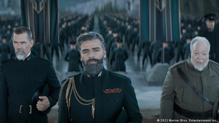 Drei Männer in Uniformen stehen vor mehreren Reihen Soldaten