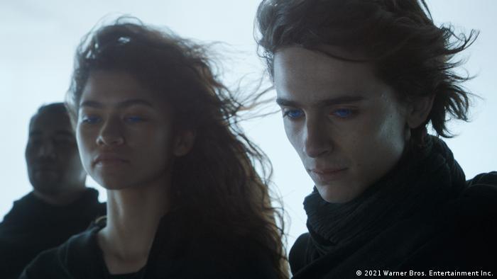 Ein junger Mann und eine junge Frau mit strahlend blauen Augen blicken nach unten, ihre Haare wehen im Wind, im Hintergrund ein weiterer Mann