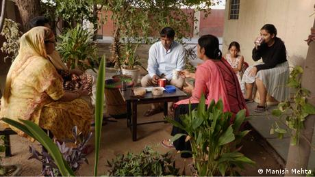 Shyam Sunder Jyani sits with his family on an outdoor terrace