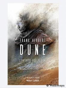 Buchcover von Frank Herberts Roman Dune. Ein junger Mann, dessen Konturen aus verwehtem Sand bestehen