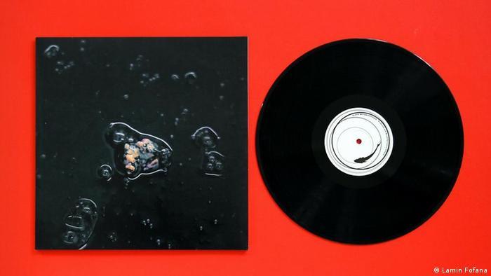 Ein Werk des Künstlers Lamin Fofana zeigt eine schwarze Plattenhülle und eine schwarze Platte auf rotem Hintergrund