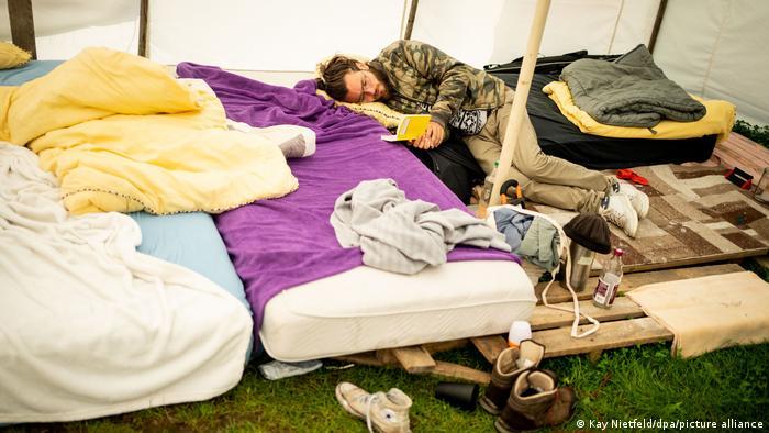 Un jeune homme lit un livre dans une tente