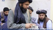 Men are pictured as Afghanistan's Taliban-controlled central bank seizes a large amount of money in cash and gold from former top government officials, including former vice president Amrullah Saleh, in Afghanistan, in this handout obtained by Reuters on September 15, 2021. Da Afghanistan Bank/Handout via REUTERS THIS IMAGE HAS BEEN SUPPLIED BY A THIRD PARTY
