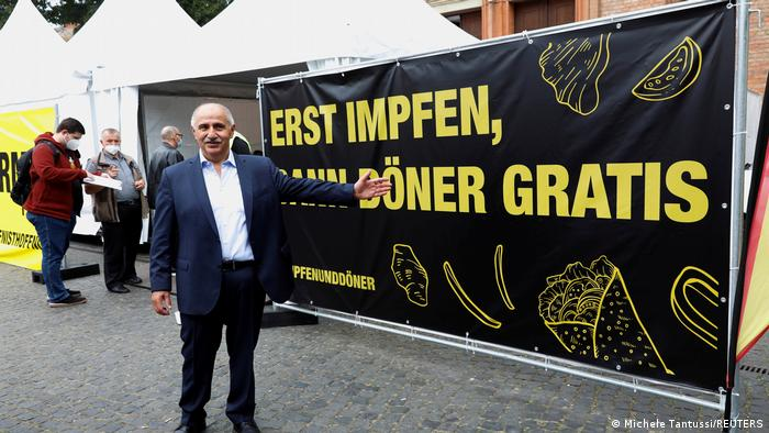 A man standing in front of a mobile vaccine station that offers free döner sandwiches.