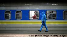 TOPSHOT - A passenger looks out the window as a medical worker walks past her carriage of a train with Ukrainians evacuated from Riga at a railway station in Kiev on March 23, 2020. - Police cordoned off the train and passenger were not allowed out the carriages for several hours after five of them were suspected of COVID-19 due the high temperature. (Photo by Sergei SUPINSKY and - / AFP) (Photo by SERGEI SUPINSKY/AFP via Getty Images)