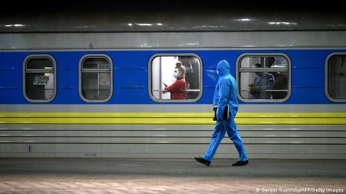 Працівник залізниці на тлі потяга в Україні