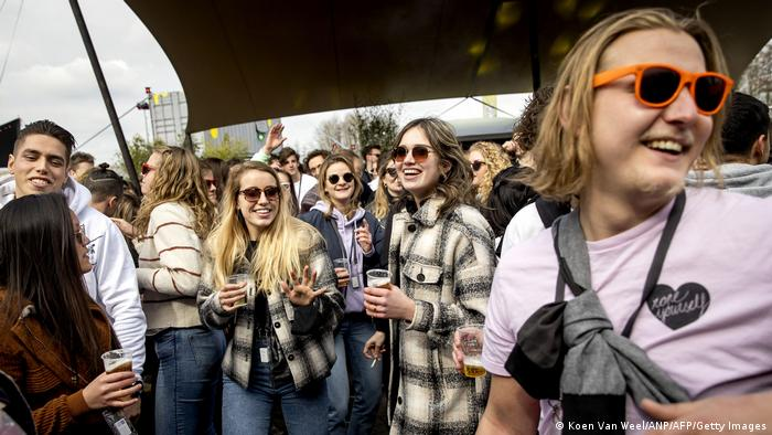 A crowd of young people holding glasses of beer