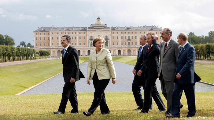 Merkel and other politicians walk across the lawn, a large building in the background
