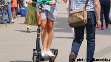 Ein Man fährt auf einem gemieteten E-Scooter durch eine belebte Fußgängerzone.