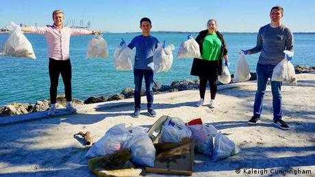 ACC activists stand with bags of garbage as they gather to clean up South Florida beaches