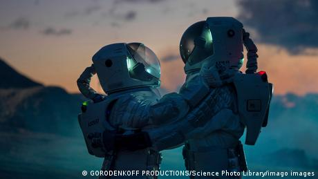 Two astornauts are hugging in full space suits
