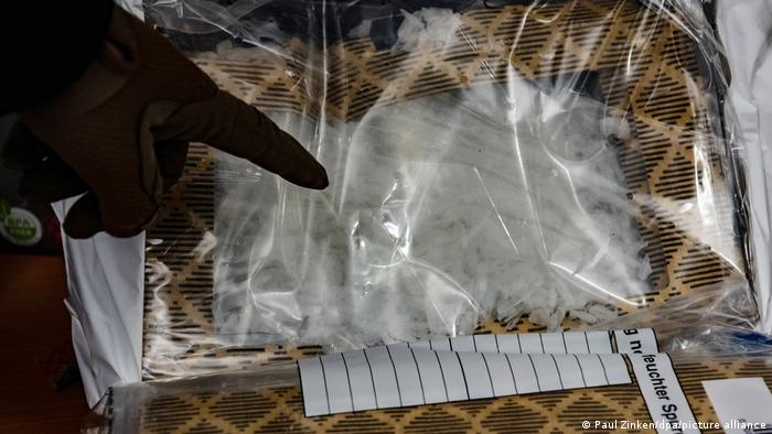 A customs officer points at a bag of meth