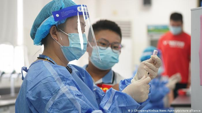 A student waits to receive a dose of COVID-19 vaccine at a vaccination point in China