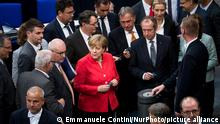 German Chancellor Angela Merkel (C) and other members of the Parliament cast their ballot for a vote during the 45th Plenary Session of Bundestag German Lower House of Parliament in Berlin, Germany on July 4, 2018. (Photo by Emmanuele Contini/NurPhoto)