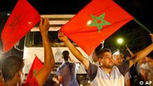 Moroccan activists wave Moroccan flags during a brief demonstration, on Tuesday night, Aug. 17, 2010 at the border crossing between Bni Anser and Melilla in a dispute over alleged police violence and racism against Moroccans entering the city. (AP Photo/Abdeljalil Bounhar)