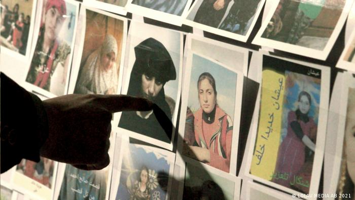 A finger pointing to a photo of a girl among several; they are portraits of missing Yazidi girls.