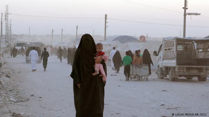 Still from film 'Sabaya': a woman wearing a niqab hold a child, people walking in the background amid a dusty refugee camp.