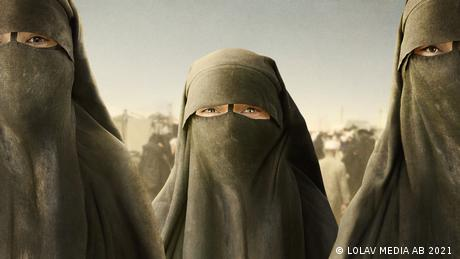 A still from the film 'Sabaya': three women wearing a niqab stare into the camera.