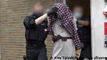 Policial conduz homem preso para fora de residência